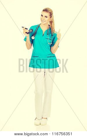 Female nurse or doctor holding glucometer
