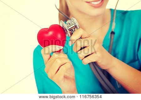 Female doctor listens to the heart through a stethoscope