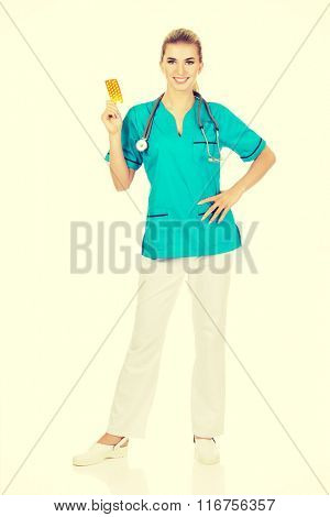 Young female nurse or doctor holding pills