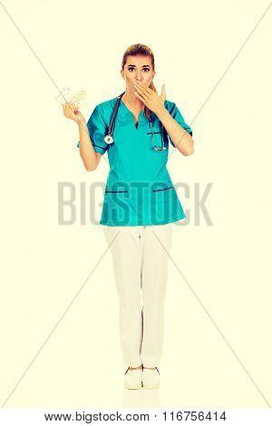 Shocked female nurse or doctor holding pills