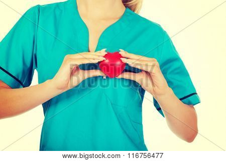 Nurse or female doctor holding red heart.