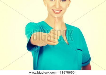 Smiling woman doctor or nurse with thumb up
