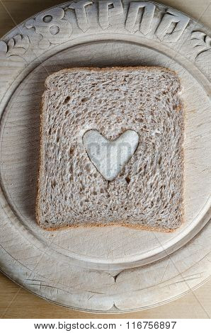 Slice Of Brown Bread With White Heart On Vintage Wooden Board