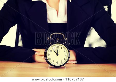 Businesswoman with alarm clock behind the desk