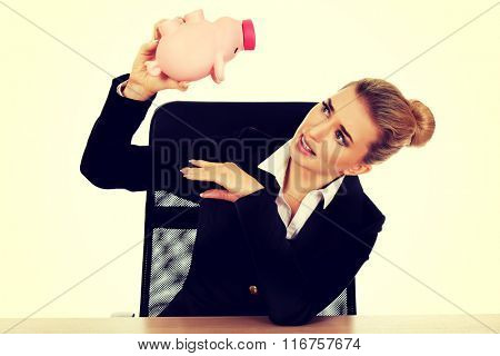 Worried businesswoman with a piggybank behind the desk