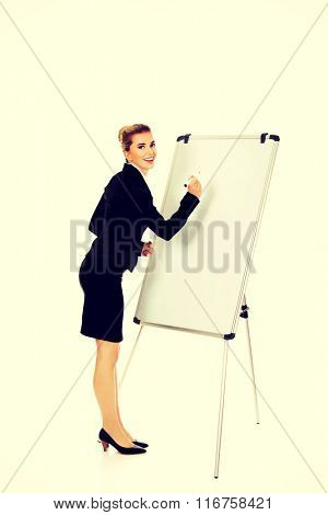 Smiling business woman writing on flipchart