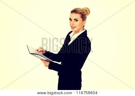 Young businessoman holding notebook and writes something