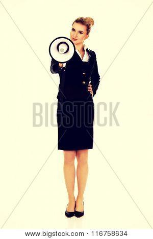 Beautiful businesswoman shouting with megaphone