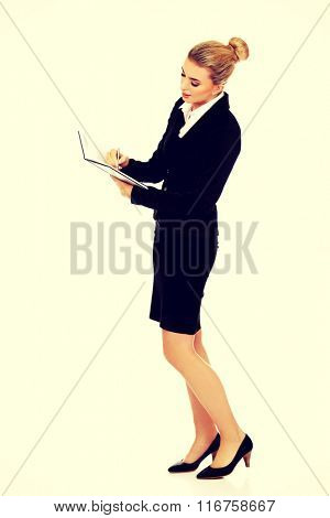 Woman holding notebook and writes something