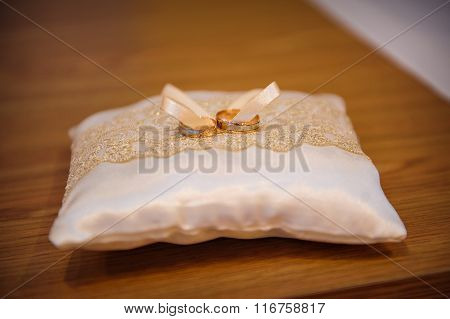 Two Wedding Gold Rings On A Cushion For The Rings