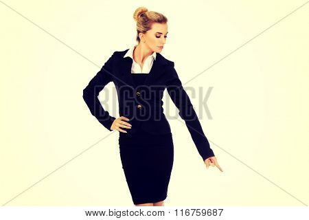 Young blonde businesswoman pointing on something