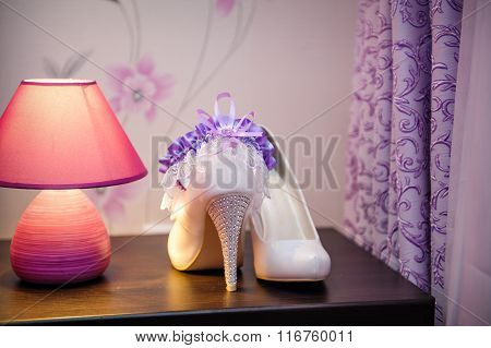 White Shoes Of The Bride And Garter On The Table