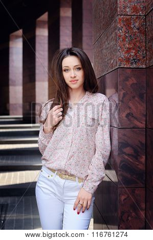 Beautiful Woman Standing Near The Stone Pillar Of A Modern Building
