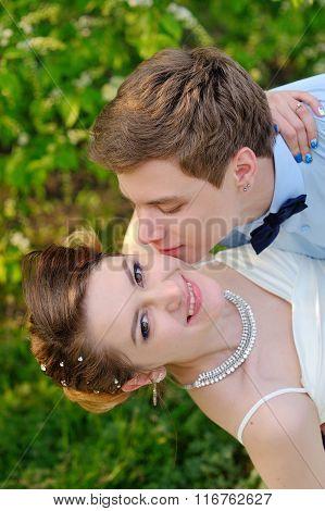 Happy Groom Kisses The Bride On Cheek. Spring Walk