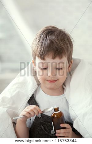 little boy drinking cough syrup