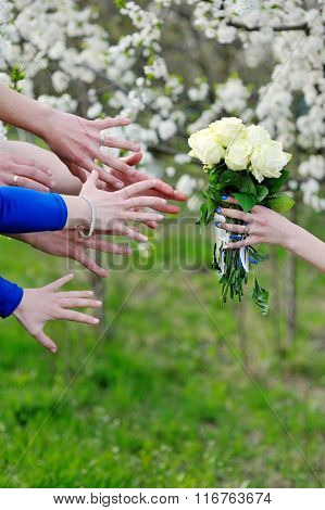 Close-up  Of Bridesmaids Stretching Their Hands To Take Wedding Bouquet