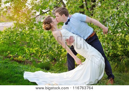 Happy Bride And Groom Kissing On Wedding In Park