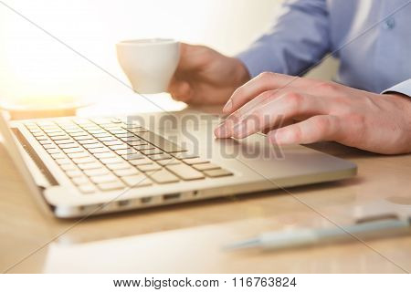 The hand on the keyboard and coffee