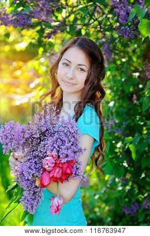 Beautiful Woman With A Bouquet Of Lilacs And Tulips Walking