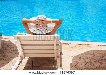 Woman In White Hat Lying On A Lounger Near The Swimming Pool