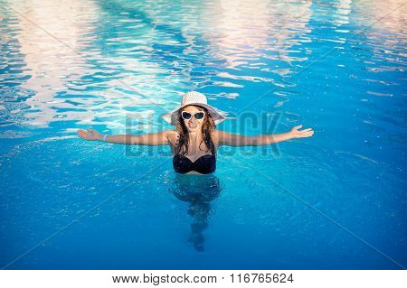 happy woman with a hat floating in a swimming pool