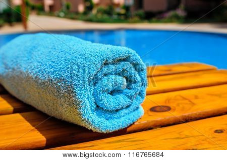 blue rolled-up towel lying on a lounger near the pool
