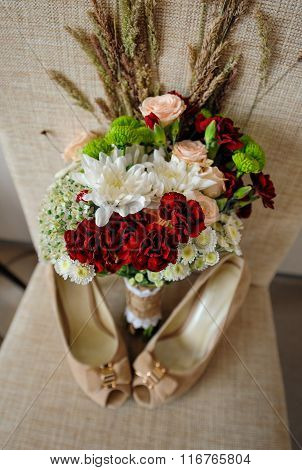 beautiful wedding bouquet and bride's shoes on the coffee table