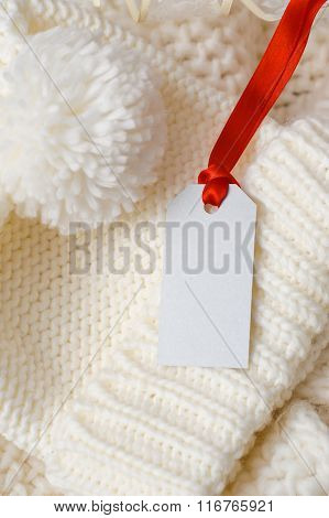 White Knitted Cap And Label With Red Ribbon