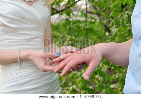Bride Puts A Wedding Ring On Groom's Finger