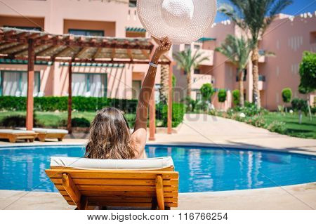 Woman Lying On A Lounger By The Pool At The Hotel