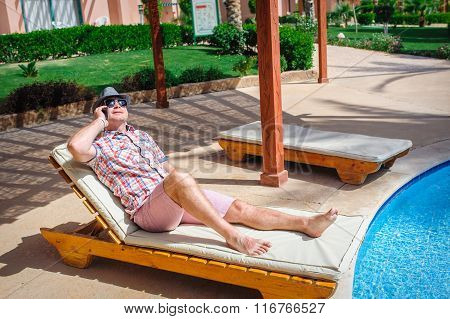 Man Lying On A Lounger And Talking On Phone