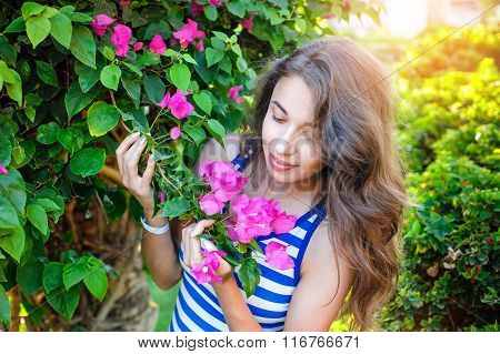 beautiful woman smelling a flower bougainvillea in the park.