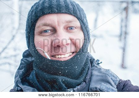 smiling man shoots selfie in winter outdoors