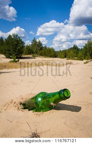 abandoned green bottle in sand