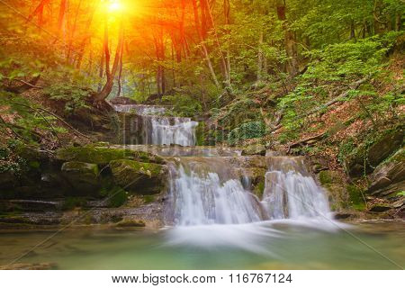 Nice waterfall on mountain river in green forest