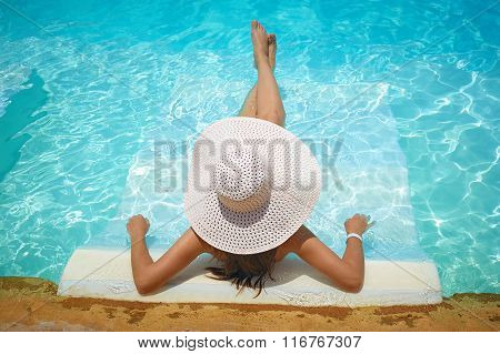 beautiful woman in a white hat sitting on the edge of the pool