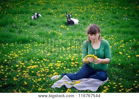 Pregnant woman weaves a wreath in the meadow