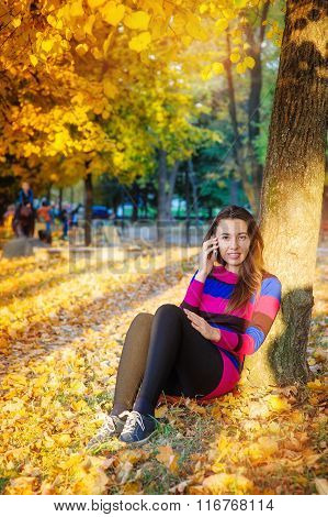 beautiful woman with phone in autumn park.
