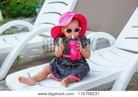 Little Girl In A Red Hat Drinking From A Mug