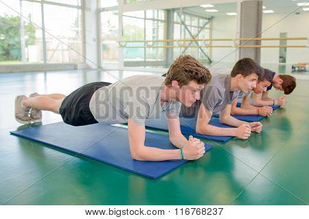 Four men exercising in plank position