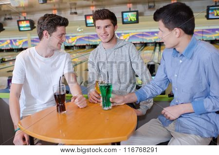 Three young men havng a drink at the bowling alley