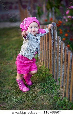 Little Girl In Pink Shoes Near The Fence