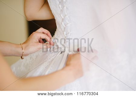 Bride Getting Dressed On Her Wedding Day