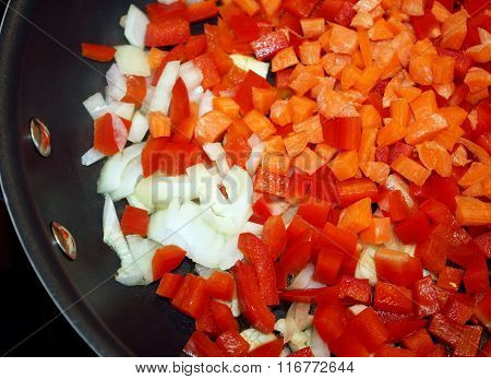 Diced red peppers, carrots and onions in a non stick skillet