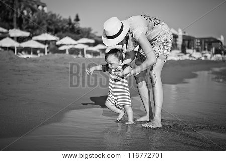 Mom Teaches A Baby To Walk On The Beach