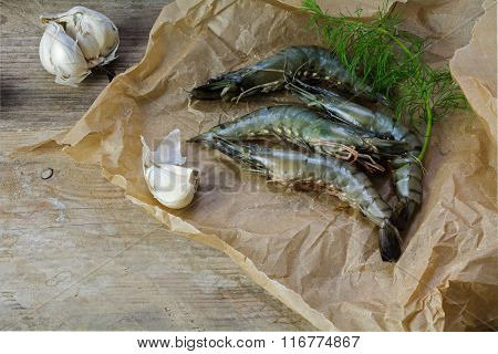 Black Tiger Prawns Fresh From The Fish Market On Paper On A Rustic Wooden Board