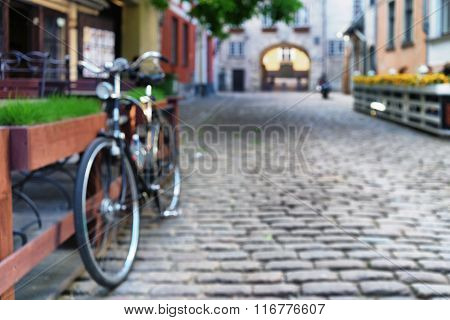 Cyclists At The Summer Cafe In The Street With Cobblestones In The Old Town
