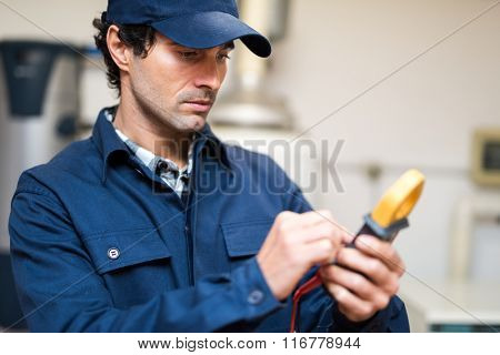 Portrait of an electrician using a tester