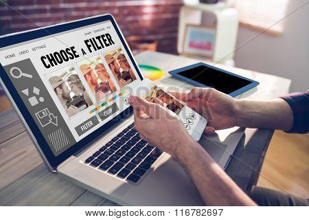 Smartphone app menu against cropped hand of graphic designer using smartphone and laptop