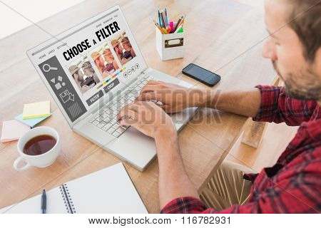 Creative businessman typing on laptop against smartphone app menu